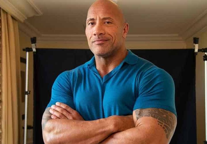 "Dwayne ""the Rock"" Johnson wearing a blue shirt with his arms folded"